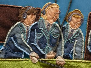 Close-up detail of embroidery showing fine details such as breast pockets, radio headphones and peoples' hairstyles.